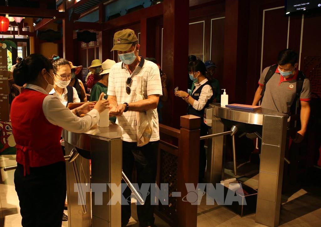 Du khách thực hiện sát khuẩn tay khi vào cửa soát vé để tham quan Khu du lịch Bà Nà Hills (Đà Nẵng)